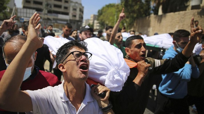 Mourners carry the the bodies of Palestinians who were killed in overnight Israeli airstrikes that hit their homes, during their funeral in Gaza City, Sunday, May 16, 2021. (AP Photo/Abdel Kareem Hana)