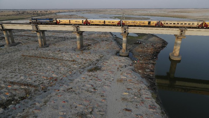 Several bodies are seen buried in shallow graves on the banks of Ganges river in Prayagraj, India. Saturday, May 15, 2021. Police are reaching out to villagers in northern India to investigate the recovery of bodies buried in shallow sand graves or washing up on the Ganges River banks, prompting speculation on social media that they were the remains of COVID-19 victims. (AP Photo/Rajesh Kumar Singh)