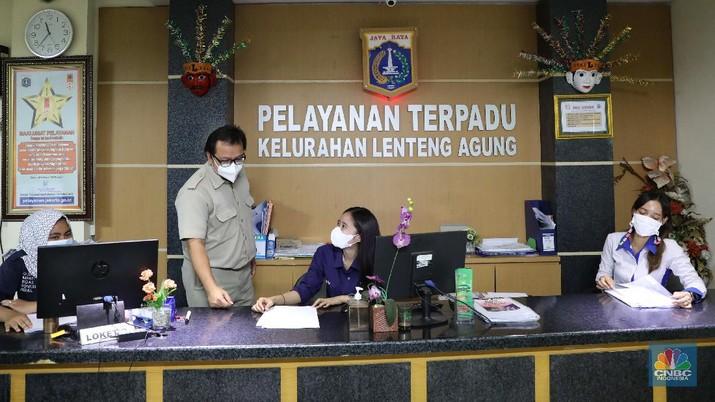 Suasana sejumlah Pegawai Negeri Sipil (PNS) Kelurahan sedang melakukan aktivitasnya di Kelurahan Lenteng Agung, Jakarta, Senin (17/5). Harin ini merupakan hari pertama para PNS masuk kembali setelah cuti bersama Idul Fitri. PNS kembali berdinas di masing-masing instansinya pada hari pertama kerja usai libur nasional dan cuti bersama Hari Raya Idul Fitri 1442 H. Seperti diketahui Pemerintah memutuskan hanya memberikan 2 hari cuti bersama bagi para Aparatur Sipil Negara (ASN) atau pegawai negeri sipil (PNS) pada 2021 ini. Salah satunya untuk Lebaran 2021. Keputusan tersebut tertuang dalam Keputusan Presiden (Keppres) Nomor 7 tahun 2021 tentang Cuti Bersama Pegawai Aparatur Sipil Negara (ASN) tahun 2021. Adapun pertama, cuti bersama Hari Raya Idul Fitri 1442 Hijriah pada 12 Mei 2021. Kedua, 24 Desember 2021 sebagai cuti bersama Hari Raya Natal. Kementerian PANRB telah menerbitkan Surat Edaran (SE) Menteri Pendayagunaan Aparatur Negara dan Reformasi Birokrasi (PANRB) No. 8/2021 tentang Pembatasan Kegiatan Bepergian ke Luar Daerah dan/atau Mudik dan/atau Cuti Bagi Pegawai ASN dalam Masa Pandemi Covid-19. Dalam aturan ini, ditegaskan jika Aparatur sipil negara (ASN) atau PNS beserta keluarganya dilarang mengambil cuti dan bepergian ke luar daerah/mudik Lebaran 2021.(CNBC Indonesia/ Muhammad Sabki)