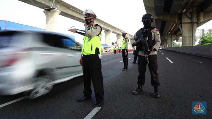 Petugas kepolisian berjaga di pos penyekatan arus balik lebaran di Tol Jakarta Cikampek KM 34B, Cikarang, Jawa Barat, Senin (17/5/2021). Direktorat Lalu Lintas (Ditlantas) Polda Metro Jaya serta sejumlah instansi terkait melakukan tes antigen secara gratis bagi pengendara yang belum memiliki surat bebas Covid-1 untuk kembali ke wilayah Jakarta dan Sekitarnya. Petugas gabungan terdiri dari TNI, Polri dan Satpol sebelumnya melakukan apel bersama, setidaknya ada 100 petugas gabungan yang ditugaskan dilokasi penyekatan.  . (CNBC Indonesia/ Tri Susilo)