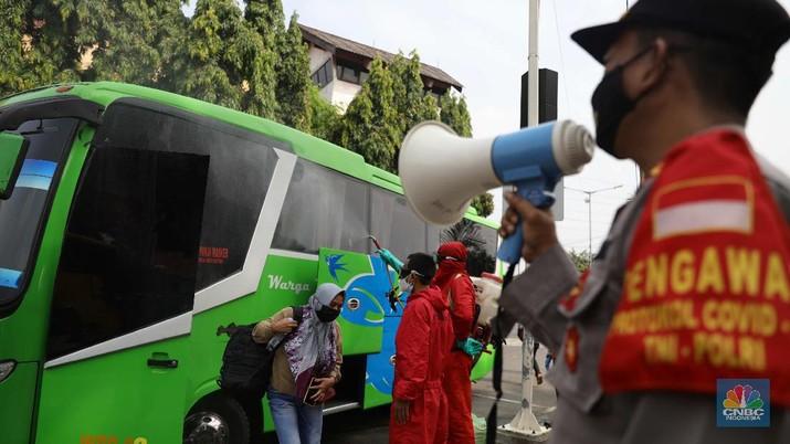 Petugas damkar menyemprot disinfektan kepada bus yang tiba dari daerah di terminal Kp Rambutan, Rabu, 19/5. Pasca berakhirnya peraturan larangan mudik Lebaran 2021, Terminal Kampung Rambutan kembali beroperasi melayani perjalanan ke luar kota dan ramai oleh penumpang tujuan Sumatra yang tidak kembali ke kampung halamannya pada Hari Raya Idul Fitri 1442 Hijriah lalu. Pantauan CNBC Indonesia pemudik dari luar Jabodetabek yang mulai berdatangan di terminal yang berlokasi di Kecamatan Ciracas, Jakarta Timur itu langsung disemprot disinfektan. Petugas juga melakukan tes rapid antigen secara acak bagi penumpang yang datang dari luar Jabodetabek. Pemandangan lain dilokasi keberangkatan juga ramai warga yang hendak pergi keluar kota. Terminal Kampung Rambutan menjadi salah satu terminal di Jakarta yang ditutup sementara selama periode larangan mudik Lebaran, 6-17 Mei 2021. Layanan bus antar kota antar provinsi (AKAP) tidak beroperasi selama periode tersebut.  (CNBC Indonesia/ Muhammad Sabki)