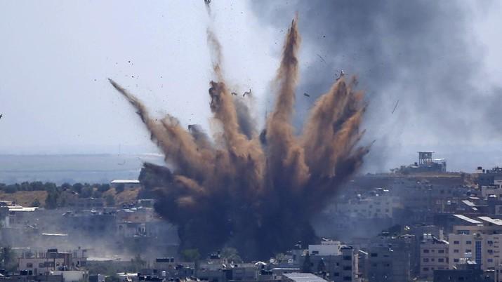 Asap membubung setelah serangan udara Israel di sebuah gedung di Kota Gaza, Kamis, 13 Mei 2021. Warga Palestina yang lelah dengan muram menandai akhir bulan suci Ramadhan, ketika Hamas dan Israel memperdagangkan lebih banyak roket dan serangan udara dan kekerasan Yahudi-Arab berkecamuk di seluruh penjuru. Israel. (AP / Hatem Moussa)