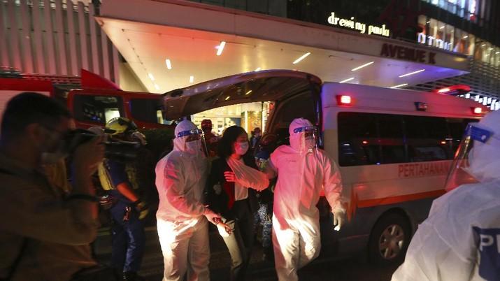 Petugas membantu penumpang yang terluka dalam insiden tabrakan dua kereta LRT di Malaysia. AP/