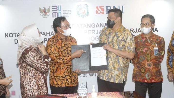 Direktur Hubungan Kelembagaan BNI Sis Apik Wijayanto (kedua kiri) dan Walikota Medan Muhammad Bobby Afif Nasution (kedua kanan) menandatangani Nota Kesepahaman (MoU) tentang Penggunaan Fasilitas Layanan Jasa Perbankan dan Dukungan Program Smart City di Jakarta, Selasa (25 Mei 2021). (Dok: BNI)