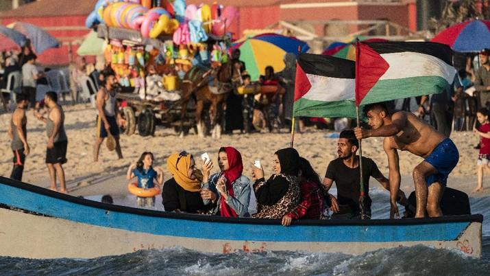 Setelah gencatan senjata, warga Palestina berlibur ke pantai  Mediterania. (AP/John Minchillo)