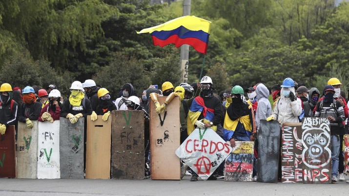 Protesters who call themselves the front line hold homemade shields during an anti-government protest in Bogota, Colombia, Friday, May 28, 2021. Colombians have taken to the streets for weeks across the country after the government proposed tax increases on public services, fuel, wages and pensions. (AP Photo/Fernando Vergara)