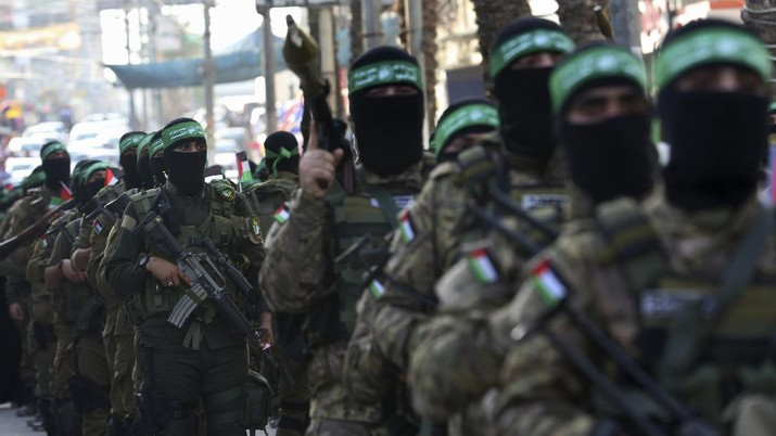 Masked militants from the Izzedine al-Qassam Brigades, a military wing of Hamas, march with their rifles a long the streets of Nusseirat refugee camp, central Gaza Strip, Friday, May 28, 2021. Arabic on the headband reads
