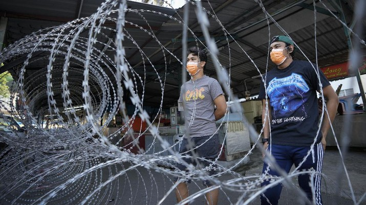 Residents wearing face mask stand behind barbwire outside Pangsapuri Permai, residential area placed under the enhanced movement control order (EMCO) due to drastic increase in the number of COVID-19 cases recorded over the past 10 days in Cheras, outskirt of Kuala Lumpur, Malaysia, Friday, May 28, 2021. Malaysia's latest coronavirus surge has been taking a turn for the worse as surging numbers and deaths have caused alarm among health officials, while cemeteries in the capital are dealing with an increasing number of deaths. (AP Photo/Vincent Thian)