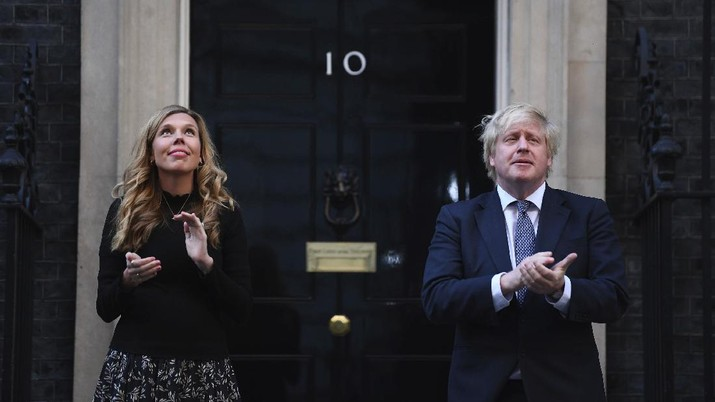 Britain's Prime Minister Boris Johnson and his partner Carrie Symonds, stand outside 10 Downing Street to join in the nationwide Clap for Carers to recognise and support National Health Service (NHS) workers and carers fighting the coronavirus pandemic, in London Thursday May 14, 2020. The highly contagious COVID-19 coronavirus has impacted on nations around the globe, many imposing self isolation and exercising social distancing when people move from their homes. (Victoria Jones / PA via AP)