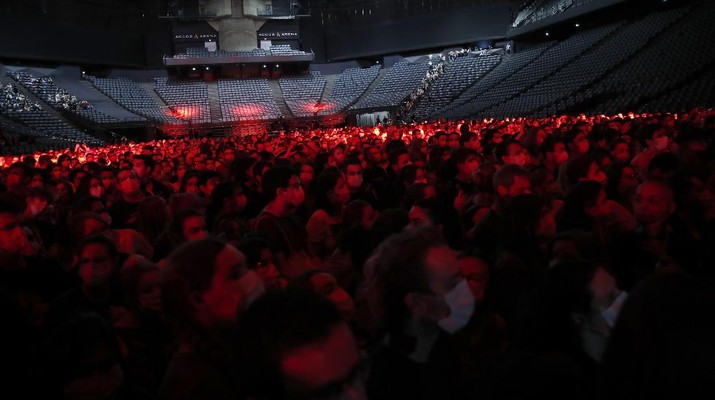 Thousands of people, masked and tested for the virus, pack inside a Paris concert hall as part of a public health experiment to prepare the country to host big events again, in Paris, Saturday, May 29, 2021. The concert in the AccorHotels Arena in eastern Paris features 1980s French rock band Indochine and DJ Etienne de Crecy. (AP Photo/Francois Mori)