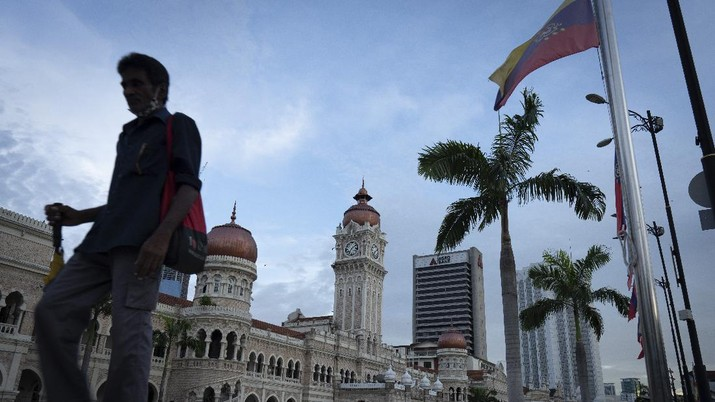 A man walks in front of Merdeka Square during the movement control order, in Kuala Lumpur, Malaysia, Saturday, May 2, 2020. Malaysia will allow most business activities to reopen from May 4. Malaysian Prime Minister Muhyiddin Yassin says the economy needs to be revived as billions have been lost during the partial lockdown that began in March.  (AP Photo/Vincent Thian)
