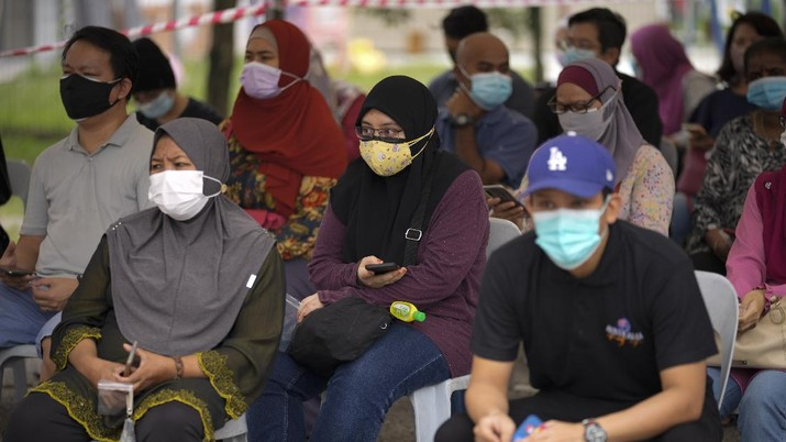 Malaysians wait outside a community hall for coronavirus testing at a COVID-19 testing center in Shah Alam, outskirts of Kuala Lumpur, Malaysia, Thursday, May 27, 2021. Malaysia's latest coronavirus surge has been taking a turn for the worse as surging numbers and deaths have caused alarm among health officials, while cemeteries in the capital are dealing with an increasing number of deaths. (AP Photo/Vincent Thian)