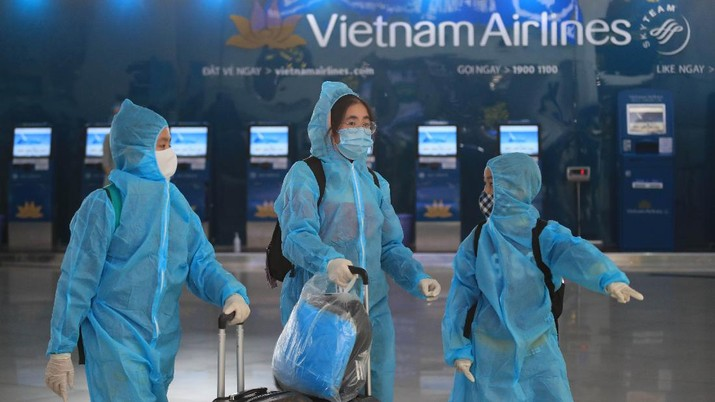 People in full protective gear walk through Noi Bai airport in Hanoi, Vietnam, Friday, Feb. 12, 2020. A fresh COVID-19 outbreak in Vietnam has slowed down business and travel during the popular lunar new year festival. (AP Photo/Hau Dinh)