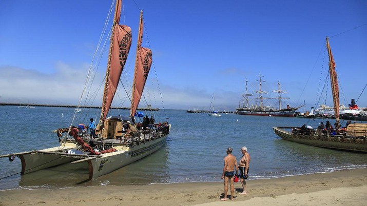 Two swimmers look over a Pacific Voyagers vaka from Fiji tied up on the beach at Aquatic Park in San Francisco, Tuesday, Aug. 9, 2011. In April, seven traditional Polynesian ocean-going vessels called vakas and their 16 member crews, set sail on a 15,000 nautical mile journey across the Pacific. The group arrived in San Francisco last week and is traveling down the West Coast to raise awareness for the health of our oceans. The vakas tied up on the beach at the park to allow the public to tour the boats. (AP Photo/Eric Risberg)