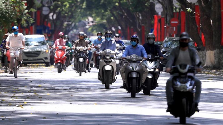 People ride motorcycles in Hanoi, Vietnam Monday, May 31, 2021. Vietnam plans to test all 9 million people in its largest city for the coronavirus and imposed more restrictions Monday to deal with a growing COVID-19 outbreak. (AP Photo/Hau Dinh)