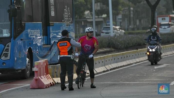 Petugas kepolisian menghalau setiap sepeda yang berada di luar jalur di kawasan Sudirman - Thamrin, Jakarta Pusat, Rabu (2/6/2021). (CNBC Indonesia/Andrean Kristianto)
