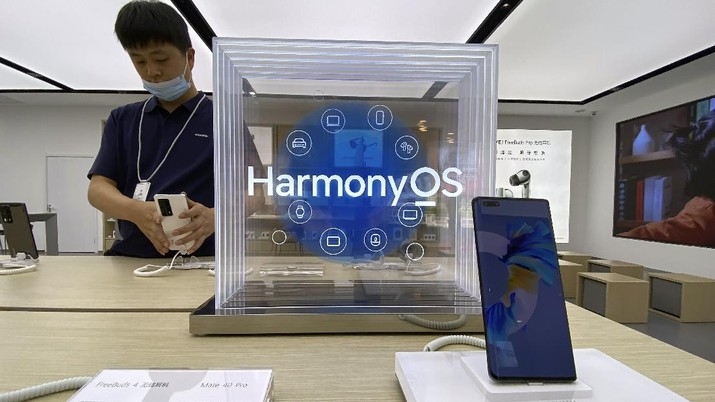 A worker adjusts a phone near a display promoting the HarmonyOS at a Huawei store in Beijing on Thursday, June 3, 2021. Huawei launched its own HarmonyOS mobile operating system on its handsets on Wednesday as it adapts to having lost access to Google mobile services two years ago after the U.S. put the Chinese telecommunications company on a trade blacklist. (AP Photo/Ng Han Guan)