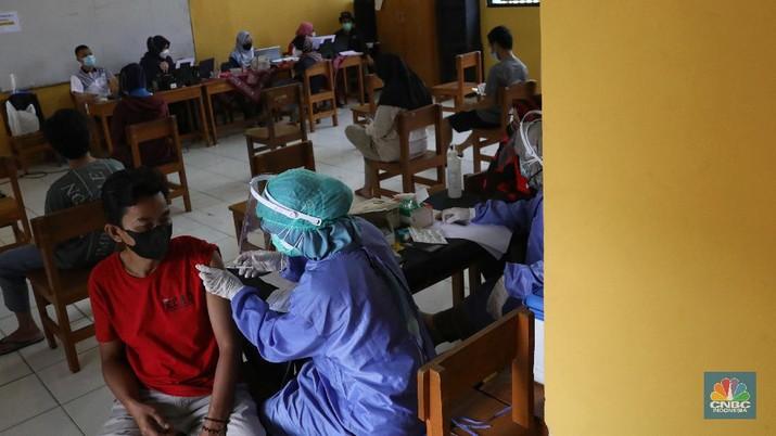 Tenaga kesehatan menyuntikan vaksin kepada warga di MTs As-Syafiiyah, Cilangkap, Jakarta, Kamis (3/6/2021). Vaksinasi massal di zona merah RT 03/ RW 03 Cilangkap akibat klaster halal bi halal itu dilakukan terhadap warga yang telah menjalani tes usap dengan hasil negatif. Vaksinasi diberikan kepada warga yang sebelumnya telah dinyatakan negatif Covid-19 hasil swab PCR. (CNBC Indonesia/Andrean Kristianto)