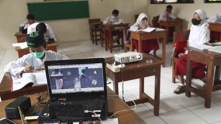 A student wearing a face mask sits spaced apart during a trial run of a class with COVID-19 protocols at an elementary school in Jakarta, Indonesia, Friday, June 4, 2021. The world's fourth-most populous country, with about 275 million people, has reported more coronavirus cases than any other Southeast Asian country. (AP Photo/Tatan Syuflana)