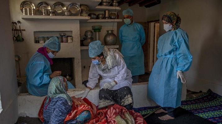 Petugas medis mendatangi rumah warga yang akan di Vaksin di India. (AP/Dar Yasin)