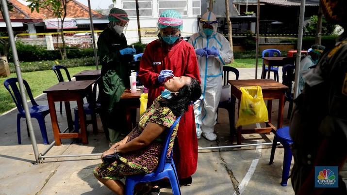 Warga menjalani test antigen untuk mendeteksi Covid-19 di Kelurahan Kayu Putih, Jakarta, Selasa (8/6). Satu RT di Kelurahan Kayu Putih, Jakarta Timur, yakni RT 11, menerapkan lockdown atau penguncian wilayah sementara usai 22 warga dinyatakan positif covid-19.kasus aktif Covid-19 di wilayah RT 11/09 tersebut berasal dari klaster keluarga, namun ada kemungkinan besar juga berasal dari klaster kerumunan mengingat di wilayah tersebut terdapat taman yang digunakan oleh para warga secara bebas dalam beraktivitas. Dalam menangani kasus aktif Covid-19 di wilayah tersebut, pihaknya tak hanya menerapkan mikro-lockdown. Namun juga turut mendistribusikan bantuan-bantuan terhadap warga yang terdampak agar dapat melewati masa pandemi Covid-19. Puluhan warga yang positif itu kini menjalani isolasi di berbagai tempat. Bagi yang bergejala, dibawa ke rumah sakit, sisanya menjalani isolasi di Wisma Atlet dan rumah masing-masing.a (CNBC Indonesia/ Muhammad Sabki)