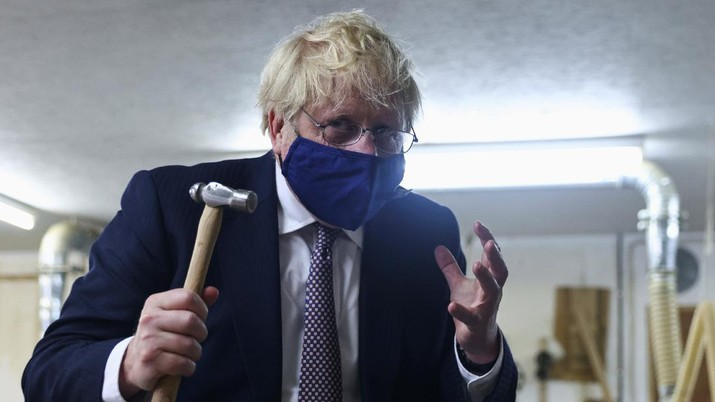 Britain's Prime Minister Boris Johnson holds a hammer after hammering a piece of Cornish tin into a model, as he visits the workshop of Scott Woyka, ahead of the G7 summit, in Falmouth, Cornwall, England, Thursday, June 10, 2021. (Tom Nicholson/Pool Photo via AP)