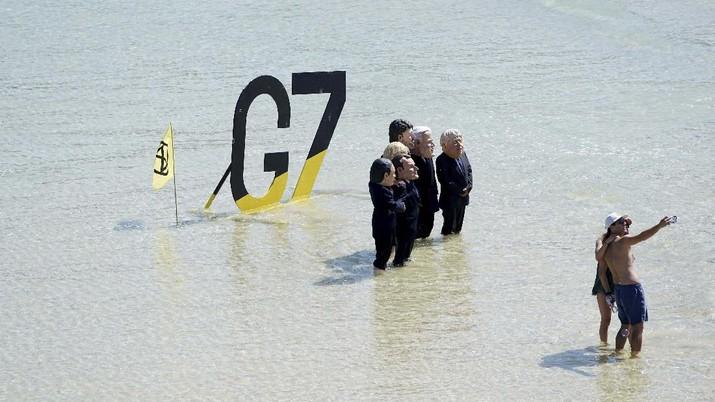 Para pengunjuk rasa mengenakan topeng yang menggambarkan para pemimpin G7 di pantai di Cornwall, Inggris. (AP/Jon Super)