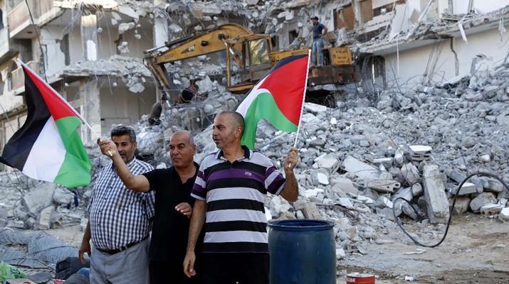 Pekerja memindahkan puing-puing bangunan yang hancur akibat serangan udara Israel, di Kota Gaza, Selasa, (15/6/2021). (AP/Tsafrir Abayov)