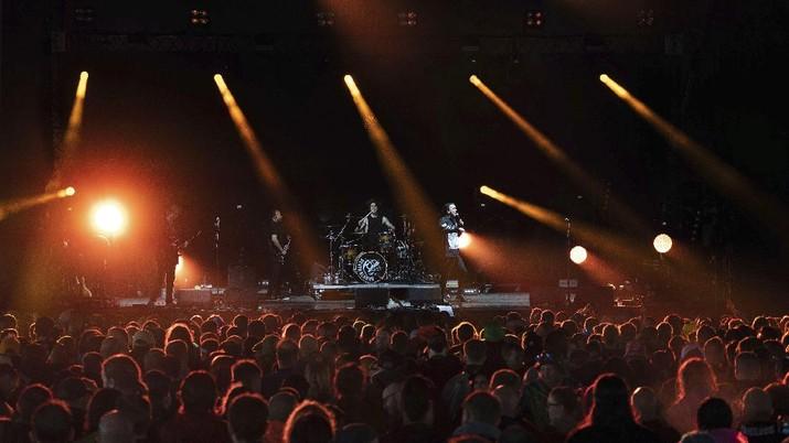 Penonton festival menyaksikan band rock Death Blooms di atas panggung pada hari pertama Download Festival di Donington Park di Castle Donington, Inggris, Jumat (18/6/2021). Festival musik dan seni selama tiga hari ini digelar sebagai ajang uji coba untuk mengkaji bagaimana Covid--19 menular. (AP/Joe Giddens)