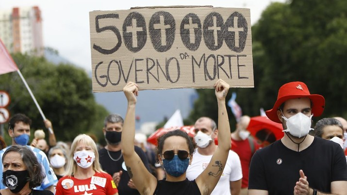 A woman wearing a protective face mask holds a sign with a message that reads in Portuguese;