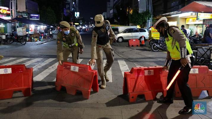 Petugas Kepolisian dan Satpol PP menutup jalan saat penerapan pembatasan mobilitas masyarakat di kawasan kuliner Jalan Sabang, Jakarta, Senin (21/6/2021). (CNBC Indonesia/ Andrean Kristianto)