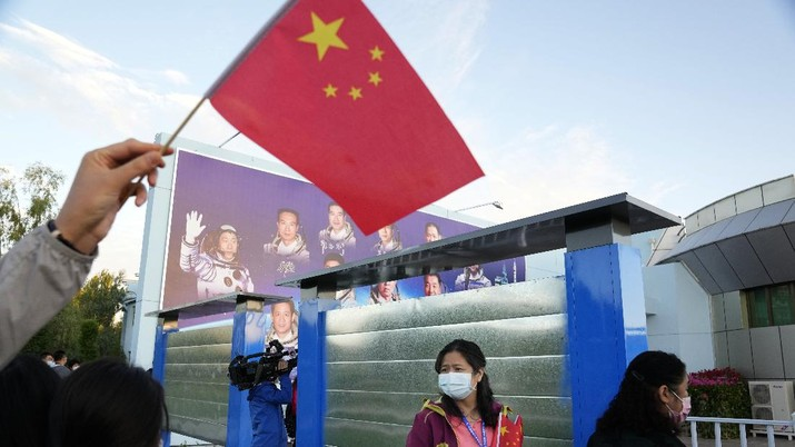 A woman holds up a Chinese flag near a board displaying China's astronauts at the Jiuquan Satellite Launch Center in Jiuquan in northwestern China, Thursday, June 17, 2021. China has launched the first three-man crew to its new space station in its ambitious programs first crewed mission in five years. (AP Photo/Ng Han Guan)
