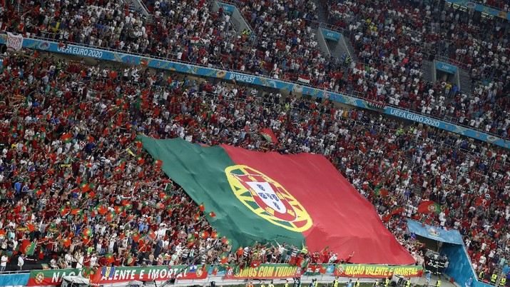Portugal supporters unfurl a large flag before the Euro 2020 soccer championship group F match between Portugal and France at the Ferenc Puskas stadium in Budapest, Hungary, Wednesday, June 23, 2021. (AP Photo/Laszlo Balogh, Pool)