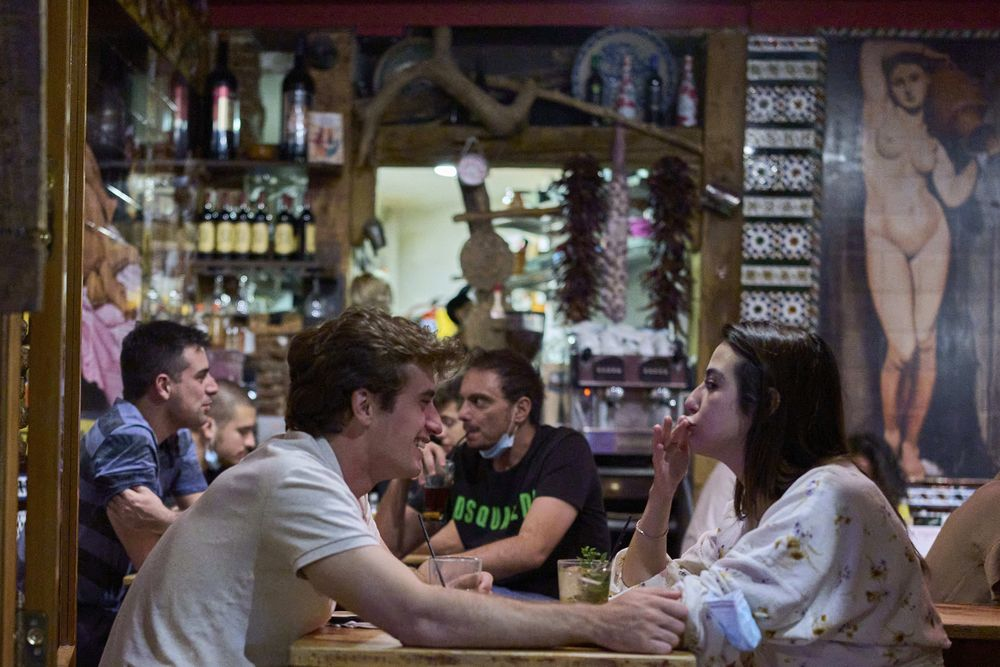 Women without wearing face masks enter into the inside of a bar in Madrid, Spain, early Saturday, June 26, 2021. Almost a year after face masks became mandatory indoors and outdoors, people from Saturday will no longer be required to wear them outside as long as they can stay at least 1.5 meters (5 feet) apart. (AP Photo/Manu Fernandez)