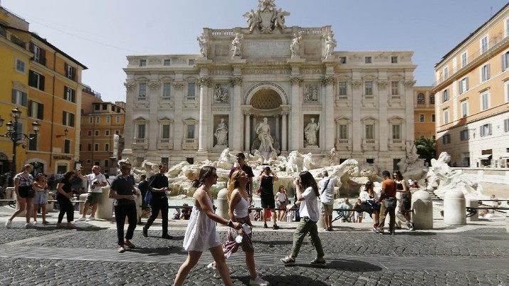People gather and walk in front of the Trevi fountain in Rome, Monday, June 28, 2021. Italians took off their face masks and breathed a huge sigh of relief on Monday as the government-imposed requirement on mask wearing outdoors was lifted. Italian Health Minister Roberto Speranza made the decision last week to lift the outdoor mask-wearing requirement on advice from Italy's Scientific Technical Committee (CTS) that made the decision based on the stabilisation of Italy Covid-19 indicators. (Cecilia Fabiano/LaPresse via AP)
