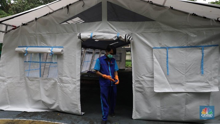 Pekerja RSUD Tarakan menyiapkan velbed di tenda darurat di SDN Negeri 02 Cideng, Jakarta, Selasa (29/6). Rumah Sakit Umum Daerah (RSUD) Tarakan kini menyiapkan tenda perawatan untuk pasien Corona di halaman IGD dan sekolah.Peminjaman lahan sekolah ini sudah berkoordinasi dengan Dinas Kesehatan DKI Jakarta. Tenda perawatan ini menyediakan 10 velbed. Sebelumnya, Dinas Kesehatan (Dinkes) DKI Jakarta menginstruksikan para direktur dan kepala rumah sakit se-DKI Jakarta menyediakan aula hingga tenda demi menampung pasien COVID-19. Arahan ini disampaikan dalam surat yang ditandatangani oleh Kepala Dinas Kesehatan DKI Jakarta Widyastuti pada 21 Juni 2021. Salah satu poin yang dipaparkan adalah meminta rumah sakit mendirikan tenda darurat berkapasitas besar di ruang terbuka di lingkungan RS.(CNBC Indonesia/ Muhammad Sabki)
