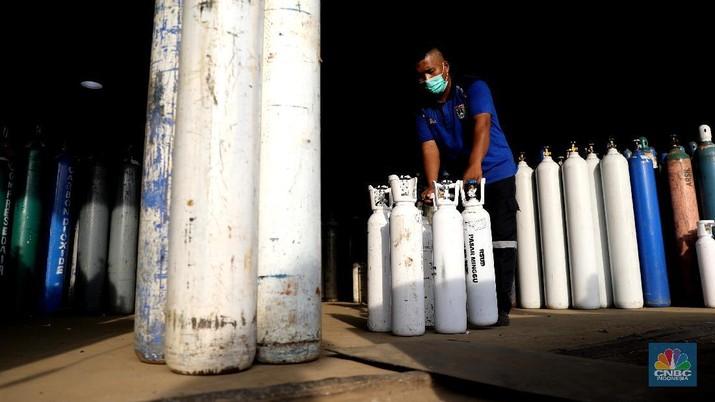 Pekerja menata tabung oksigen di tempat pengisian oksigen PT Aneka Gas Industri, Cakung, Jakarta Timur, Rabu (30/6/2021). Pemprov DKI Jakarta mengerahkan kendaraan dari berbagai Satuan Kerja Perangkat Daerah (SKPD) atau kedinasan di DKI Jakarta untuk membantu mendistribusikan oksigen ke berbagai Rumah Sakit rujukan Covid-19.  Hal tersebut dilakukan untuk mempercepat sirkulasi tabung oksigen yang sempat mengalami kelangkaan beberapa hari lalu. Pantauan CNBC Indonesia beberapa truk dari perangkat daerah seperti Dishub DKI hingga SDA ikut mengantri mengambil oksigen. Antrian pengisian dilokasi tersebut juga memakan waktu lama. Salah satu sopir truk mengaku ia mengantri dari jam 7 pagi hingga pukul 15.30 belum juga bisa diangkut. Karena antrian truk yang begitu ramai. Tempat pengisian Oksigen ini melayani hingga 24 jam.  (CNBC Indonesia/ Muhammad Sabki)