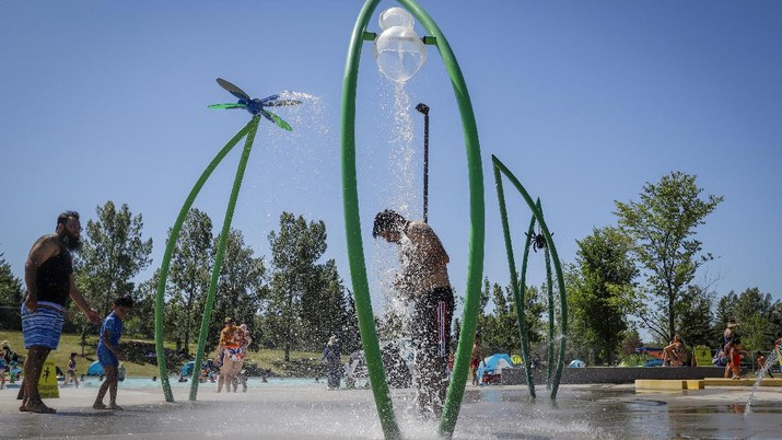 A man stands under a water feature trying to beat the heat at a splash park in Calgary, Alberta, Wednesday, June 30, 2021. Environment Canada warns the torrid heat wave that has settled over much of Western Canada won't lift for days. (Jeff McIntosh/The Canadian Press via AP)