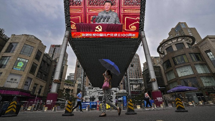 People walk past a large video screen outside a shopping mall showing Chinese President Xi Jinping speaking during an event to commemorate the 100th anniversary of China's Communist Party at Tiananmen Square in Beijing, Thursday, July 1, 2021. China's ruling Communist Party is marking the 100th anniversary of its founding with speeches and grand displays intended to showcase economic progress and social stability to justify its iron grip on political power. (AP Photo/Andy Wong)