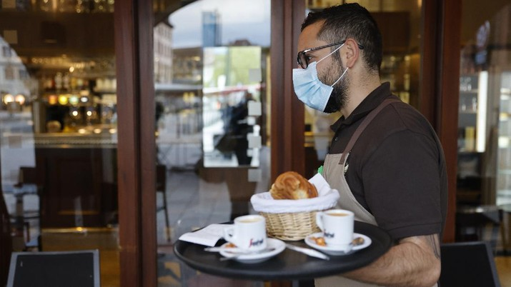 A waiter carries cafes and croissants in a café Wednesday, May, 19, 2021 in Strasbourg, eastern France. It's a grand day for the French. Café and restaurant terraces are reopening Wednesday after a shutdown of more than six months deprived people of what feels like the essence of life — sipping coffee and wine with friends outdoors — to save lives during the coronavirus pandemic. (AP Photo/Jean-Francois Badias)
