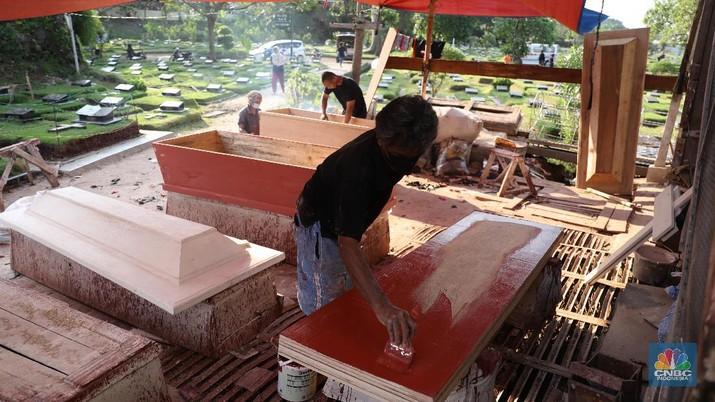 Pekerja menyelesaikan pesanan peti jenazah di Kawasan TPU Pondok Kelapa, Jakarta, Jumat, (2/7). Lonjakan angka kematian karena virus Covid-19 membuat pesanan peti jenazah mengalami peningkatan pesanan. Dalam rentang waktu seminggu ini, pihak Sahabat Duka telah membuat hampir sebanyak 250 peti jenazah.  CV Sahabat Duka yang berbasis di Tempat Pemakaman Umum (TPU) Pondok Kelapa, Jakarta Timur bak kejatuhan durian runtuh. Pesanan peti mati setiap harinya terus bertambah.