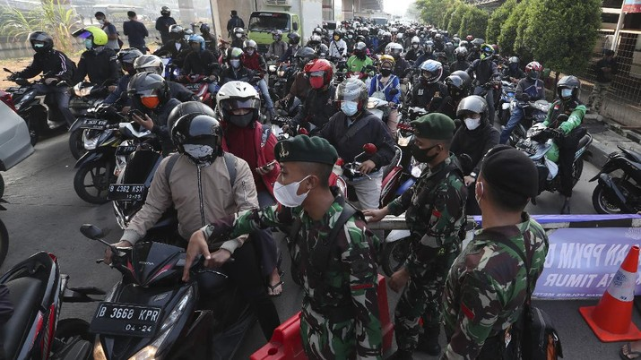 Aparat berjaga pos penyekatan PPKM Darurat di Kalimalang, Jakarta, Senin (5/7/2021). (AP/Achmad Ibrahim)