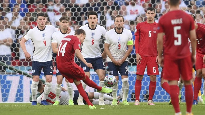 Denmark's Mikkel Damsgaard, left, scores his side's opening goal from a free kick during the Euro 2020 soccer semifinal match between England and Denmark at Wembley stadium in London, Wednesday, July 7, 2021. (Laurence Griffiths/Pool Photo via AP)
