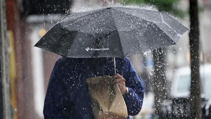 A pedestrian uses an umbrella to shield himself during a downpour from Tropical Storm Elsa, Friday, July 9, 2021, in Portland, Maine. Elsa is the earliest fifth-named storm on record, said Brian McNoldy, a hurricane researcher at the University of Miami. (AP Photo/Robert F. Bukaty)