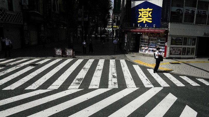 A man waiting to cross the street is seen from a shuttle bus ahead of the 2020 Summer Olympics, Monday, July 12, 2021, in Tokyo. (AP Photo/Jae C. Hong)