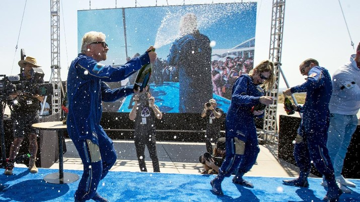 Virgin Galactic founder Richard Branson, left, sprays champagne to his crew members while celebrating their flight to space from Spaceport America near Truth or Consequences, N.M., Sunday, July 11, 2021. (AP Photo/Andres Leighton)