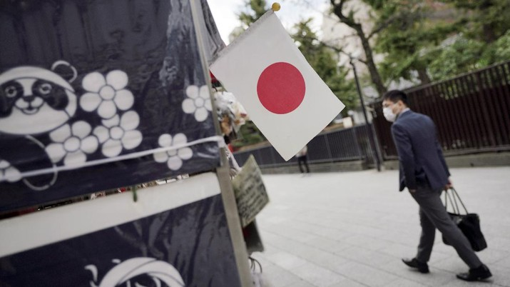 A man wearing a protective mask to help curb the spread of the coronavirus walks near a Japanese flag at a shopping arcade at Asakusa district Thursday, Oct. 22, 2020, in Tokyo. (AP Photo/Eugene Hoshiko)
