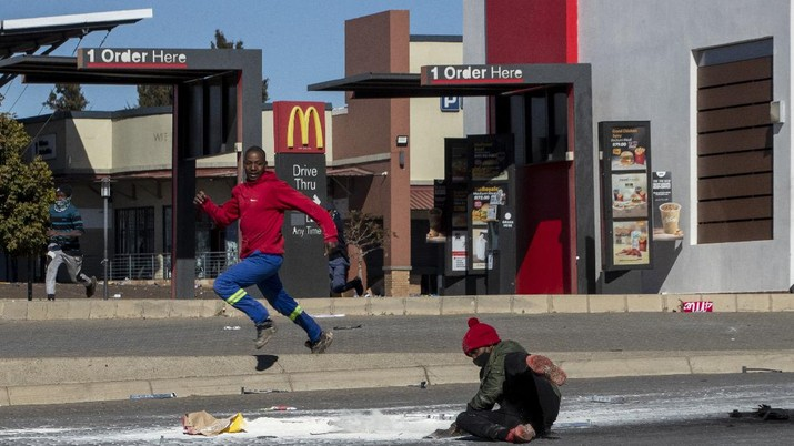 Looters run as policer officers chassis at a shopping centre in Soweto, Johannesburg, Tuesd in Johannesburg, South Africa, Tuesday, July 13, 2021. South Africa's rioting continued Tuesday with the death toll rising to 32 as police and the military struggle to quell the violence in Gauteng and KwaZulu-Natal provinces. The violence started in various parts of KwaZulu-Natal last week when Zuma began serving a 15-month sentence for contempt of court. (AP Photo/Themba Hadebe)