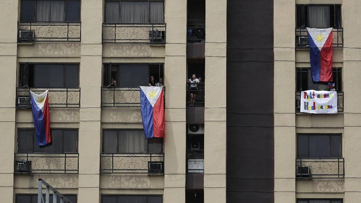 Residents display Philippine flags from their windows as they pay tribute to health workers, essential personnel and security forces during an enhanced community quarantine to prevent the spread of the new coronavirus in Manila, Philippines, Sunday, April 12, 2020. The new coronavirus causes mild or moderate symptoms for most people, but for some, especially older adults and people with existing health problems, it can cause more severe illness or death. (AP Photo/Aaron Favila)