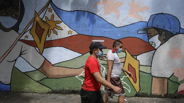 People wearing protective masks to prevent the spread of the coronavirus walk past a mural showing a Philippine flag and Filipinos wearing masks in Manila, Philippines on Wednesday, Oct. 21, 2020. The Philippines lifted a ban on non-essential foreign trips by Filipinos Wednesday but the immigration bureau said the move did not immediately spark large numbers of departures for tourism and leisure. (AP Photo/Aaron Favila)
